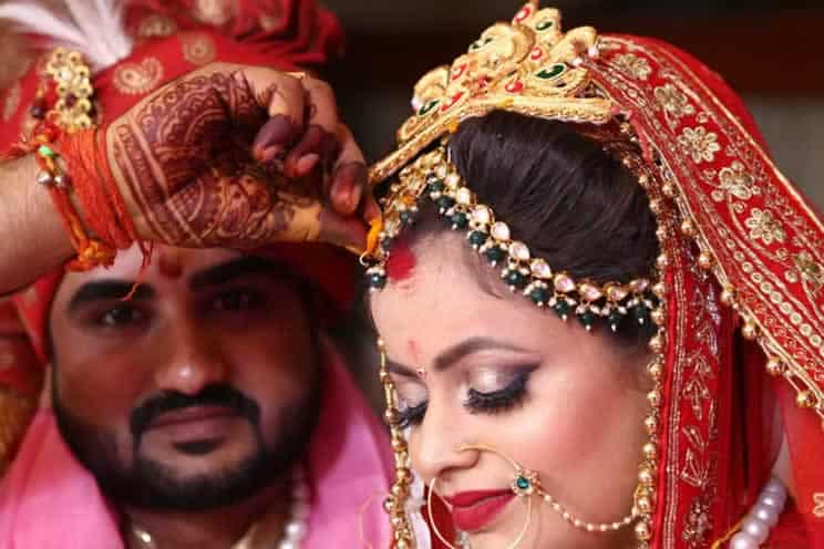 hindu groom putting blessing on brides head