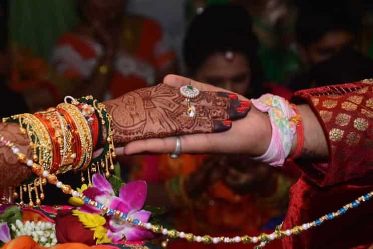 hindu brides hand placed on top of hindu grooms hand