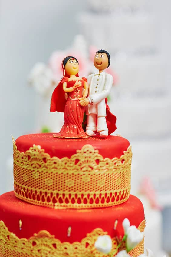 Beautiful red and yellow wedding cake in Indian style with bride and groom figurines on top
