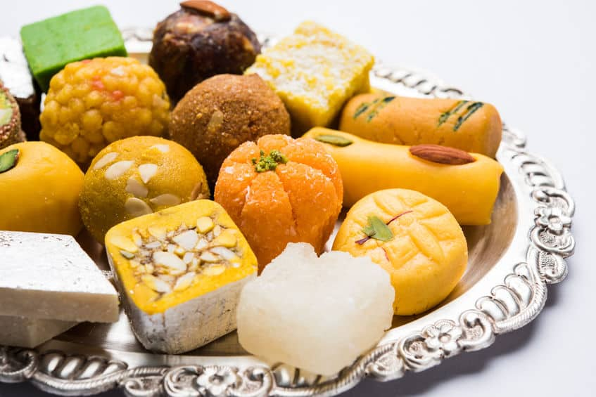 Indian sweets served in silver plate. variety of Peda, burfi, laddu in decorative plate