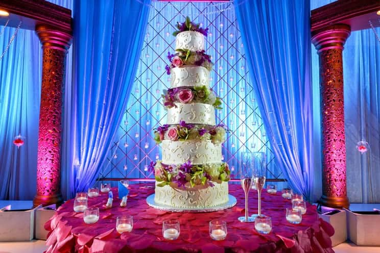 image of a tall tiered wedding cake at indian wedding