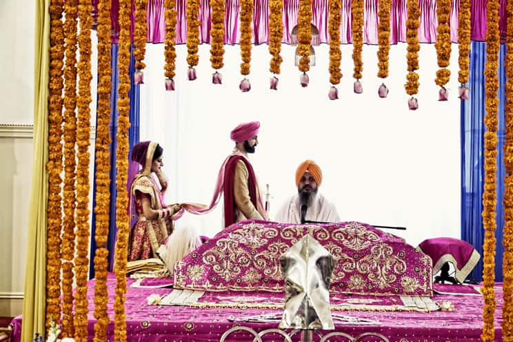 Sikh bride following Sikh groom around the Sikh holy book in Sikh temple