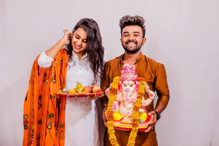 Hindu couple giving blessing to Ganesh statue