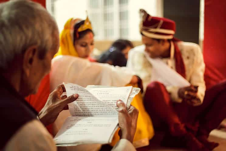 Mantras Ritual during Hindu Marriage at Mandap in presence of Bride Groom. Camera focus is on mantra book in the hand of the priest