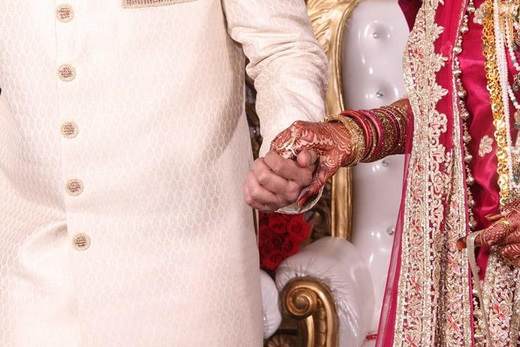 Hindu wedding couple holding hands at an Indian wedding