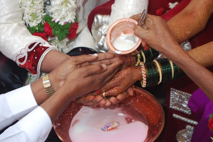 Coconut milk being poured over hindu brides and grooms hands