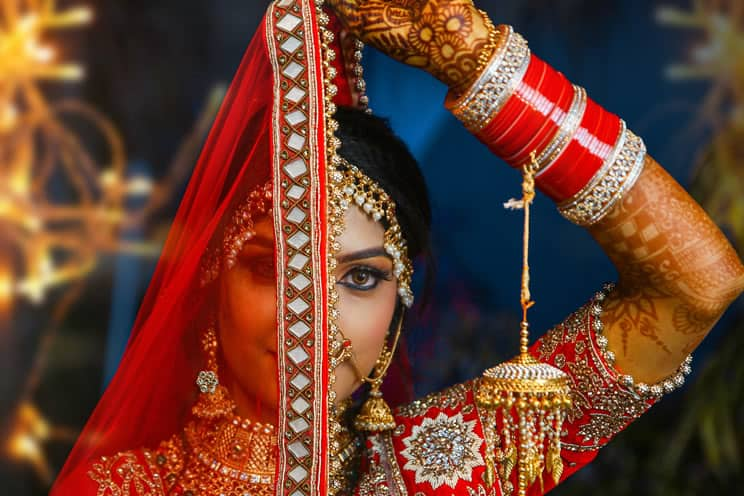 Hindu wedding bride holding chunni across her face