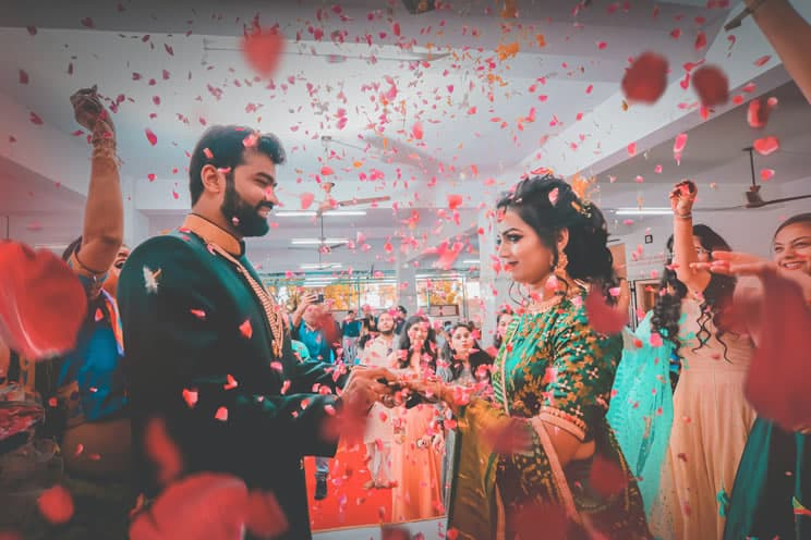 hindu bride and groom holding hands with indian wedding guests showering them with flower petals