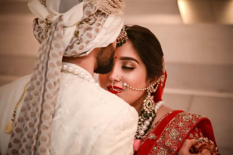Hindu groom kissing Hindu bride