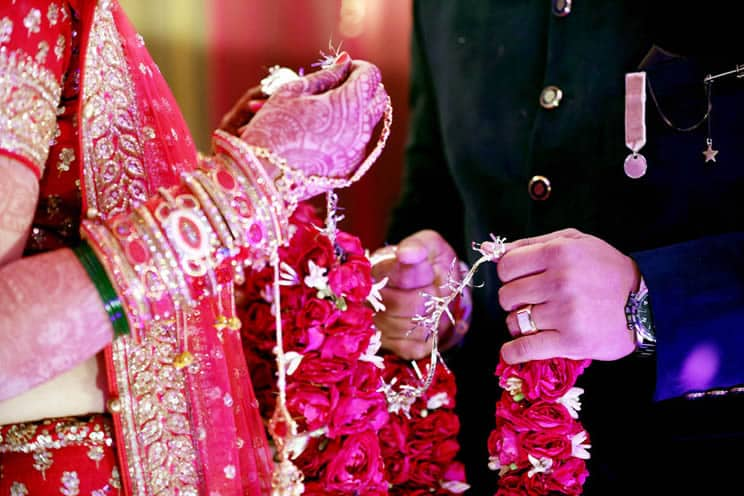 Hindu bride and groom standing opposite each other at Indian wedding and making their pheras
