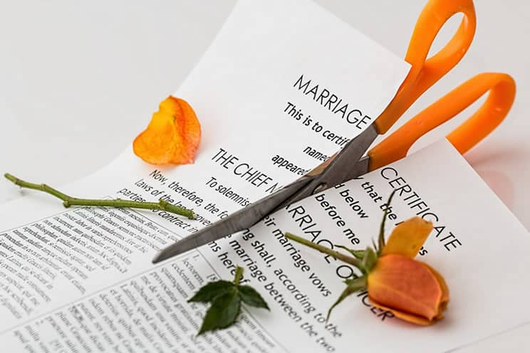 Photo of scissors cutting up marriage certificate and rose.